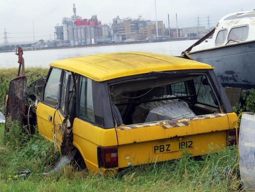 Picture of abandoned yellow Range Rover on Swanscombe Marshes at the peninsular on mainly derelcit brownfield land with the odd decaying boat and motor vehicle