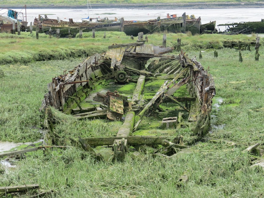 Picture of Derelict sailing barge originally used to transport locally dug clay to cement works.Many barges ended up as houseboats at the adjacent Hoo Marina though as their condition deteriorated they are hulked on the salt marsh and left to further decay.