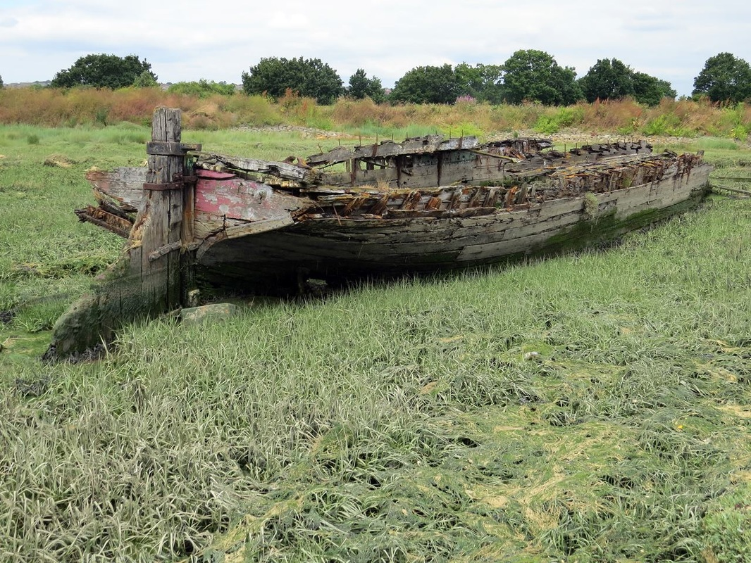 Picture of decayed wreck of a sailing barge hulked near Hoo Marina on the River Medway in Kent.