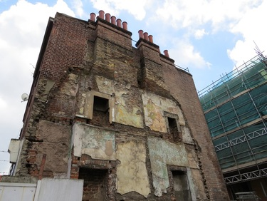 Half demolished building in Whitechapel with old fireplaces exposed