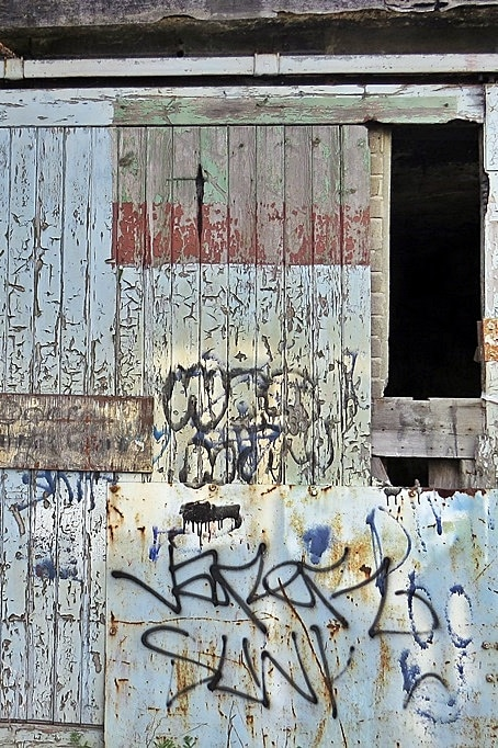 Peeling paint and rotting wood on doors of derelict building in Silvertown, East London