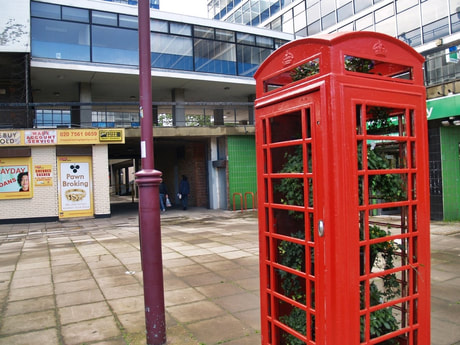 Disused red telephone box in Archway with plants growing in it (popup greenhouse?)