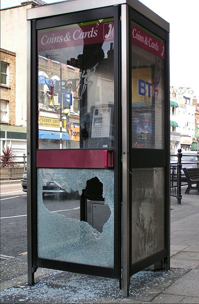 smashed glass panel of phone box in Mile End