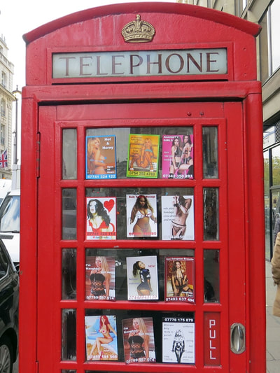 Prostitute calling cards in red phone in Piccadilly, Central London