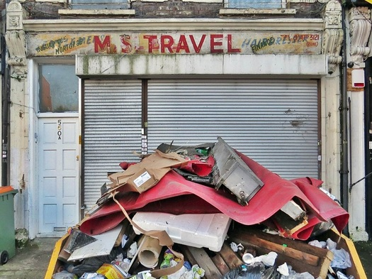 Closed down shop in Manor Park, East London. The fading sign reveals clues of travel, mortgages and hairdressers.