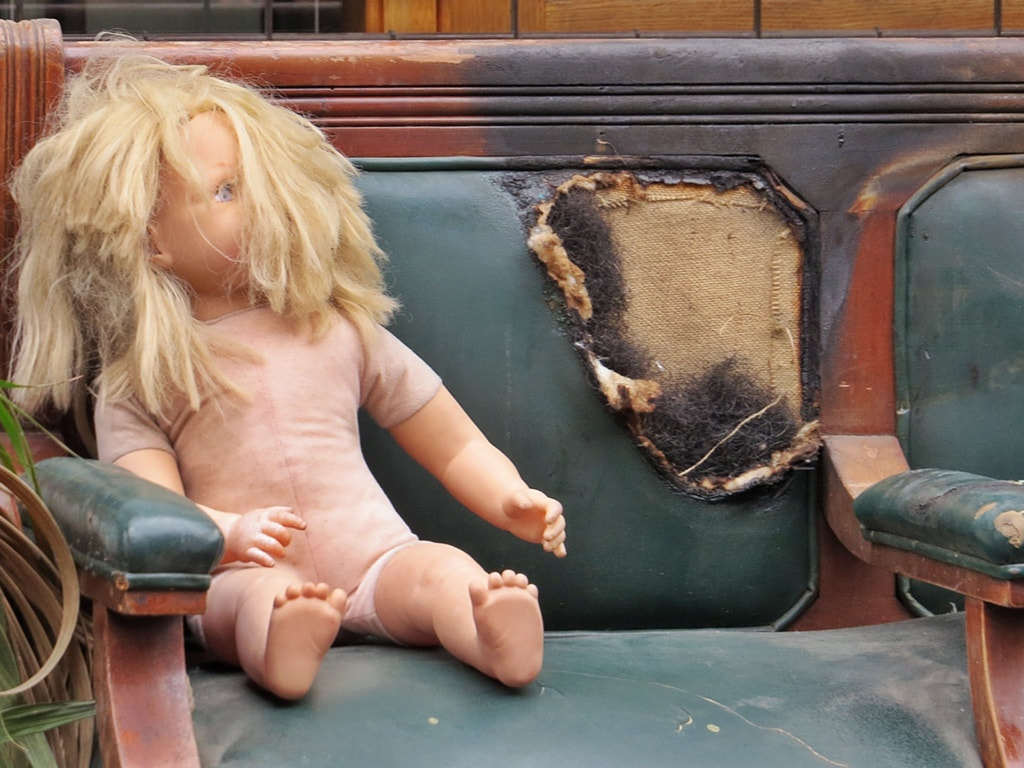 spurned child's dolly on burnt chair in East London