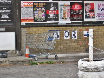 Abandoned supermarket shopping trolley on brownfield site in London