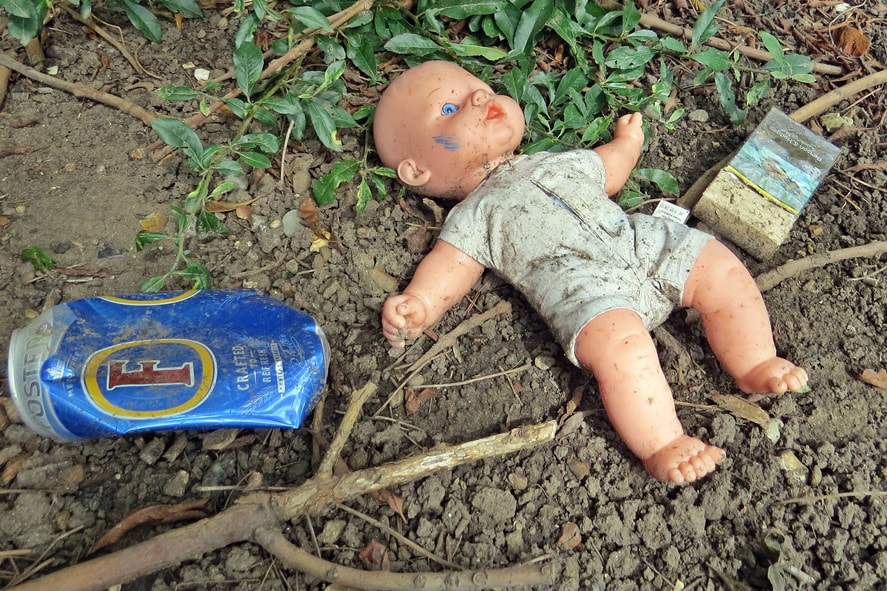 Sad unloved, abandoned child's doll surrounded by cigarettes and alcohol