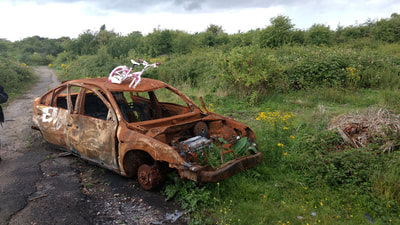 Child's pink bike abandoned on top of burnt out car in Dartford, Kent