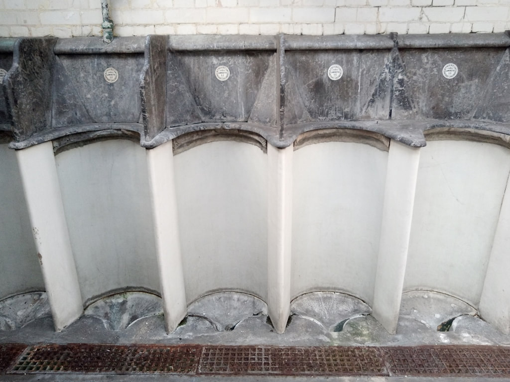 "Disused public toilets in Kennington with white marble urinals with black marble modesty screens and ceramic roundels inscribed ""B Finch and Co Limited, Sanitary Engineers, Lambeth SE"""