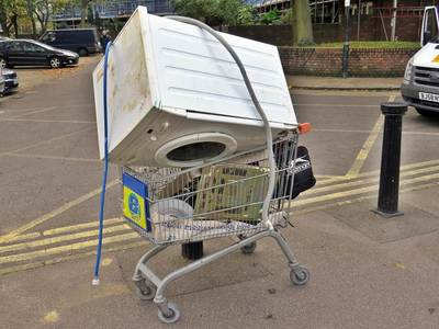 supermarket shopping trolley containing a dumped washing machine in  London
