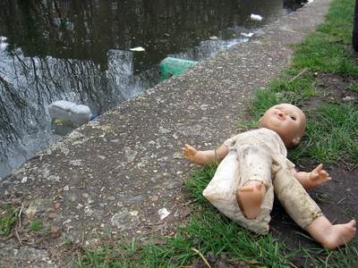 unwanted child's doll flytipped beside Regent's Canal in Hackney