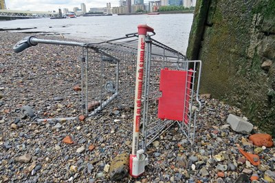 discarded Iceland supermarket shopping trolley on the Thames foreshore at low tide