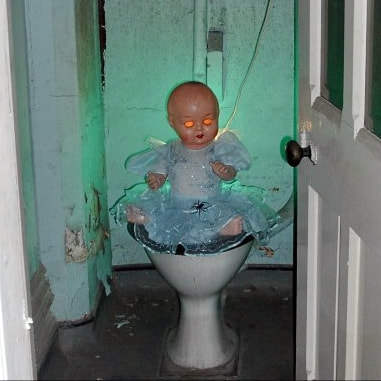 Doll sitting on the toilet in abandoned St Pancras Hotel