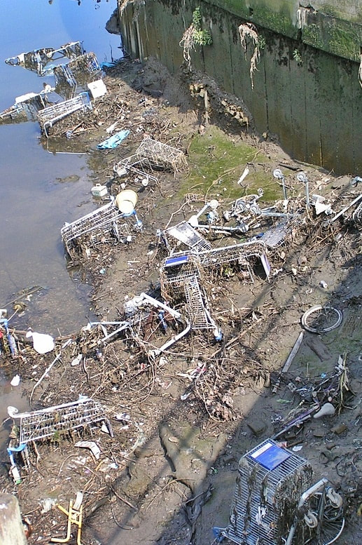Abandoned supermarket shopping trolleys disposed of in the City Mill River in Stratford near the Olympic Park